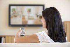 Frau in überwachendem Fernsehen des Wohnzimmers Stockbild