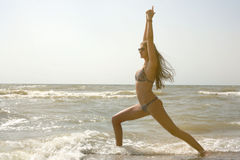 Frau übt Yoga und Meditation in der Heldposition auf dem Strand im Meer Stockfotos