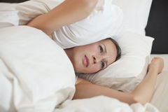 Frau abgedeckt mit Kissen Stockbild