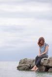 Frau allein und deprimiert an der Küste Stockfotografie