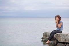 Frau allein und deprimiert an der Küste Lizenzfreies Stockfoto