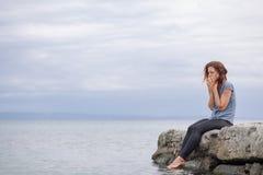 Frau allein und deprimiert an der Küste Stockbild