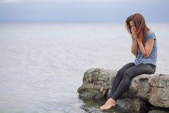 Frau allein und deprimiert an der Küste Stockbilder