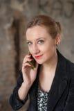 Frau am Altbau sprechend am Telefon Stockbild