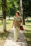 Frau alterte kräftig Wege entlang einem Weg in einem Park, der in der Leinenkleidung und mit dem Fliegenhaar gekleidet wurde stockbild
