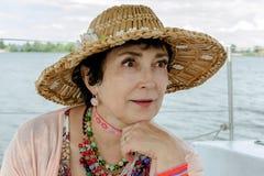 Frau alterte und trug einen Strohhut auf dem Hintergrund des Wassers Lizenzfreie Stockfotos