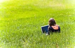 Frau angeschlossen auf dem Gras Stockfotografie