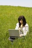 Frau angeschlossen auf dem Gras Lizenzfreie Stockfotografie