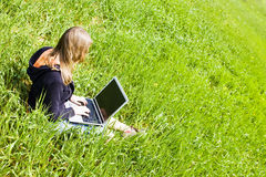 Frau angeschlossen auf dem Gras Stockfotos