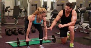 Frau anhebender Barbell mit ihrem Trainer an crossfit Sitzung stock footage