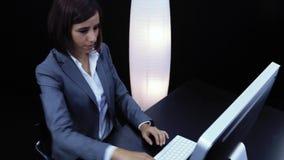 Frau arbeitet am Computer und am Zeigen einer Karte mit Text stock video