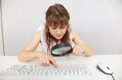 Frau arbeitet mit Tastatur mittels des Vergrößerungsglases Lizenzfreie Stockfotos