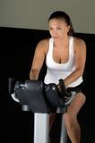 Frau auf Übungs-Fahrrad Lizenzfreies Stockbild