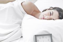 Frau auf Bett morgens mit einem Borduhrklingeln Stockfotos