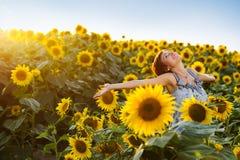 Frau auf blühendem Sonnenblumefeld Lizenzfreie Stockbilder