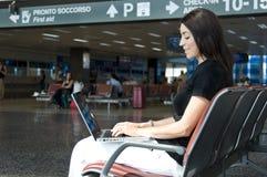 Frau auf Computer im Flughafen Stockbild