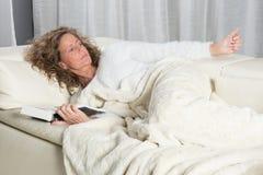 Frau auf Couch ein Buch lesend Stockbilder
