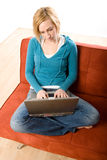 Frau auf Couch mit Laptop Stockbild