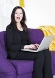 Frau auf Couch mit Laptop stockfotos