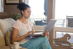 Frau auf Couch mit Laptop Lizenzfreies Stockbild
