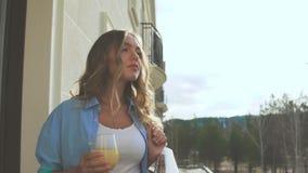 Frau auf dem Balkon am frühen Morgen und Orangensaft der Getränke stock footage
