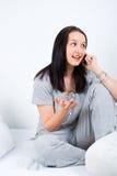 Frau auf dem Bett, das Gespräch durch Telefon hat Lizenzfreie Stockfotografie