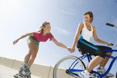 Frau auf dem Fahrrad, das Freund auf Inliner zieht Lizenzfreie Stockfotografie