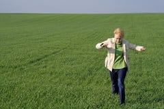 Frau auf dem Feld am Frühling Stockfotografie