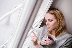 Frau auf dem Fensterbrett, das eine Tasse Tee hält Stockfoto