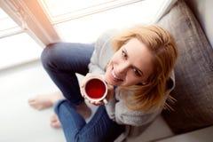 Frau auf dem Fensterbrett, das eine Tasse Tee hält Lizenzfreie Stockfotos