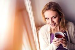 Frau auf dem Fensterbrett, das eine Tasse Tee hält Lizenzfreie Stockfotografie
