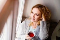 Frau auf dem Fensterbrett, das eine Tasse Tee hält Stockfotografie