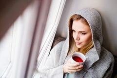Frau auf dem Fensterbrett, das eine Tasse Tee hält Stockbild