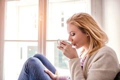 Frau auf dem Fensterbrett, das eine Teeschale, trinkend hält Lizenzfreie Stockfotos