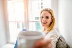 Frau auf dem Fensterbrett, das einen Tasse Kaffee hält Lizenzfreies Stockfoto