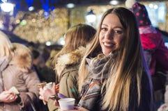 Frau auf dem festlichen Weihnachtsmarkt nachts Glückliche Frau, die dem städtischen Weihnachtenvibe nachts glaubt stockbild