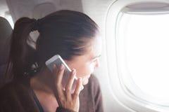 Frau auf dem Flugzeug mit dem Smartphone, der in der Öffnung schaut Stockfotografie