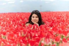 Frau auf dem Gebiet auf roten Tulpen Lizenzfreie Stockfotos