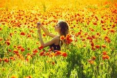 Frau auf dem Gebiet der Mohnblume selfie Foto mit Telefon machend lizenzfreie stockfotos