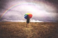 Frau auf dem Gebiet mit buntem Regenschirm im Regen Lizenzfreie Stockfotografie