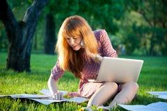 Frau auf dem Gras mit Notizbuch und Papier Stockbilder