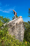 Frau auf dem großen Stein während des Wanderns stockbild