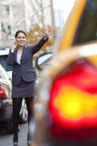 Frau auf dem Handy, der ein gelbes Rollen-Fahrerhaus hagelt Lizenzfreie Stockbilder