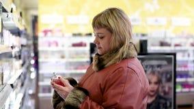 Frau auf dem Hintergrund von Regalen mit Kosmetik und Parfümen wählt Parfüm stock footage