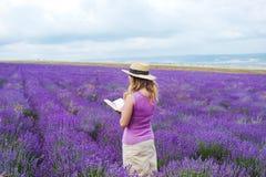 Frau auf dem Lavendelgebiet mit Buch Stockbilder