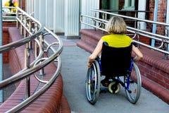 Frau auf dem Rollstuhl, der die Plattform einträgt lizenzfreie stockfotos