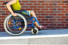 Frau auf dem Rollstuhl, der die Plattform einträgt stockbild