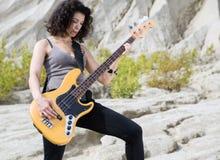 Frau auf dem sandigen Hintergrund, der mit Gitarre aufwirft Lizenzfreie Stockbilder