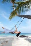 Frau auf dem Schwingen auf dem Strand im weißen Kleid Stockbild
