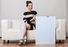 Frau auf dem Sofa, das leere Schautafel hält Stockfotos